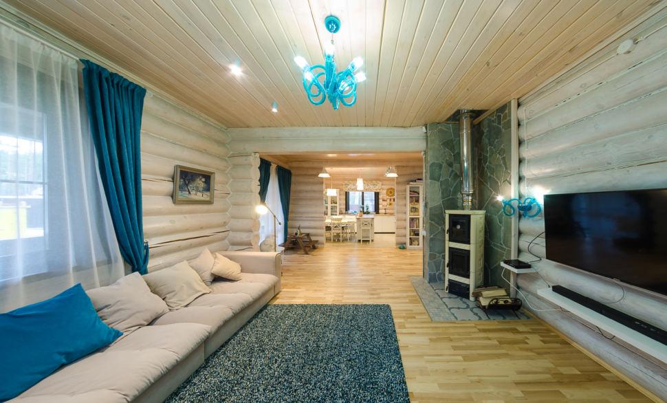 интерьер гостиной в стиле прованс, акцентные бирюзовые портьеры, светлый диван, телевизор, бревна