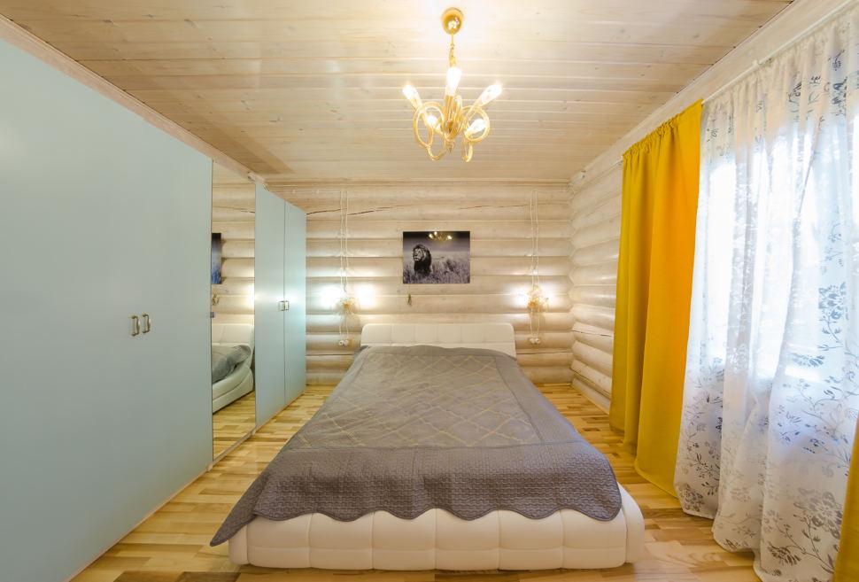 дизайн спальни в теплых тонах, желтые портьеры, текстиль серого цвета, брус, шкаф, подвесные светильники