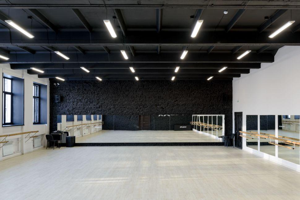 Фотография интерьера танцевального зала 210 кв.м, белый логотип, зеркала, черный окрашенный кирпич, черный потолок, подвесные светильники, двери, стол