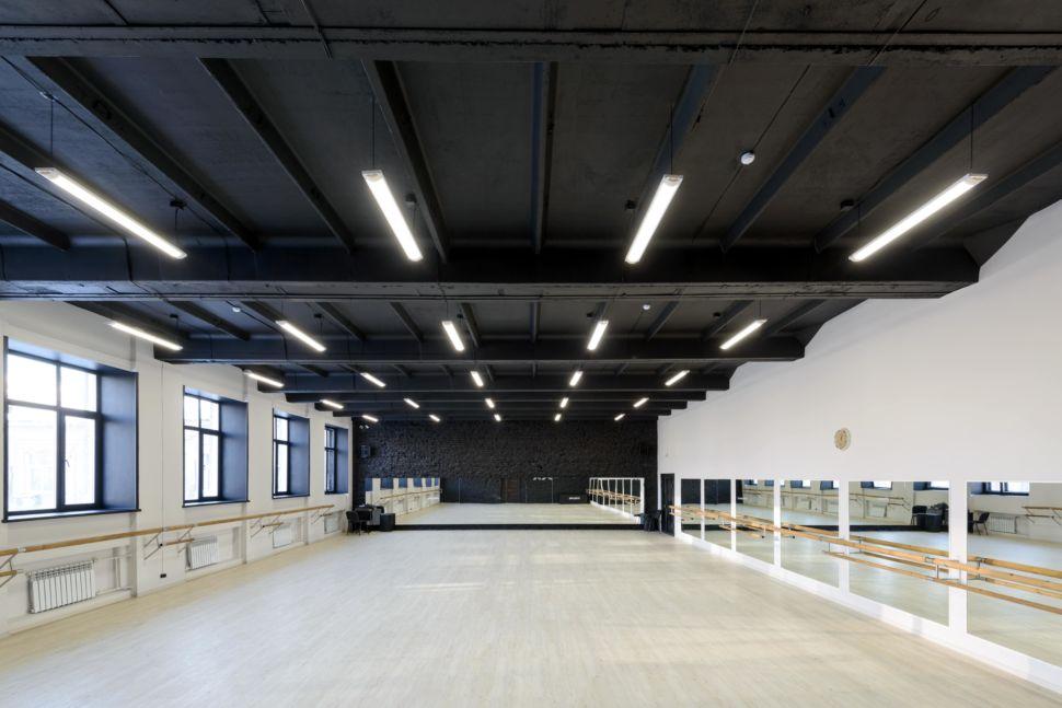 Фотография интерьера танцевального зала 210 кв.м, белый логотип, зеркала, черный окрашенный кирпич, черный потолок, подвесные светильники, двери, радиаторы