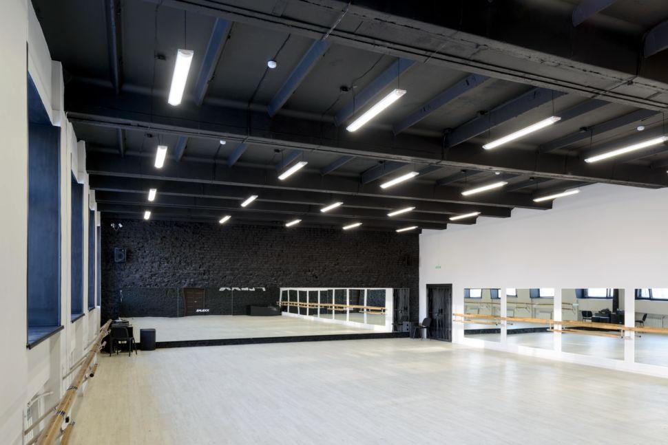 Фотография интерьера танцевального зала 210 кв.м, белый логотип, зеркала, черный окрашенный кирпич, черный потолок, подвесные светильники, двери, балки