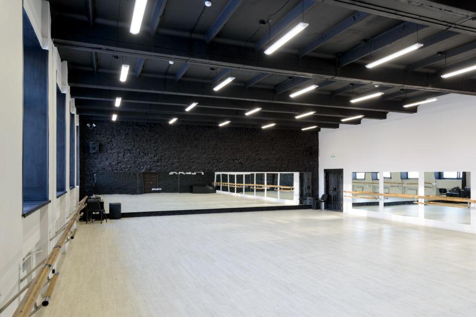 Дизайн зеркал танцевального зала 210 кв.м, белый логотип, зеркала, черный окрашенный кирпич, черный потолок, подвесные светильники, двери, стулья