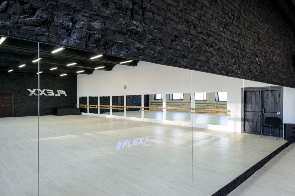Фотография интерьера танцевального зала 210 кв.м, белый логотип, зеркала, черный окрашенный кирпич, черный потолок, подвесные светильники, двери, стул