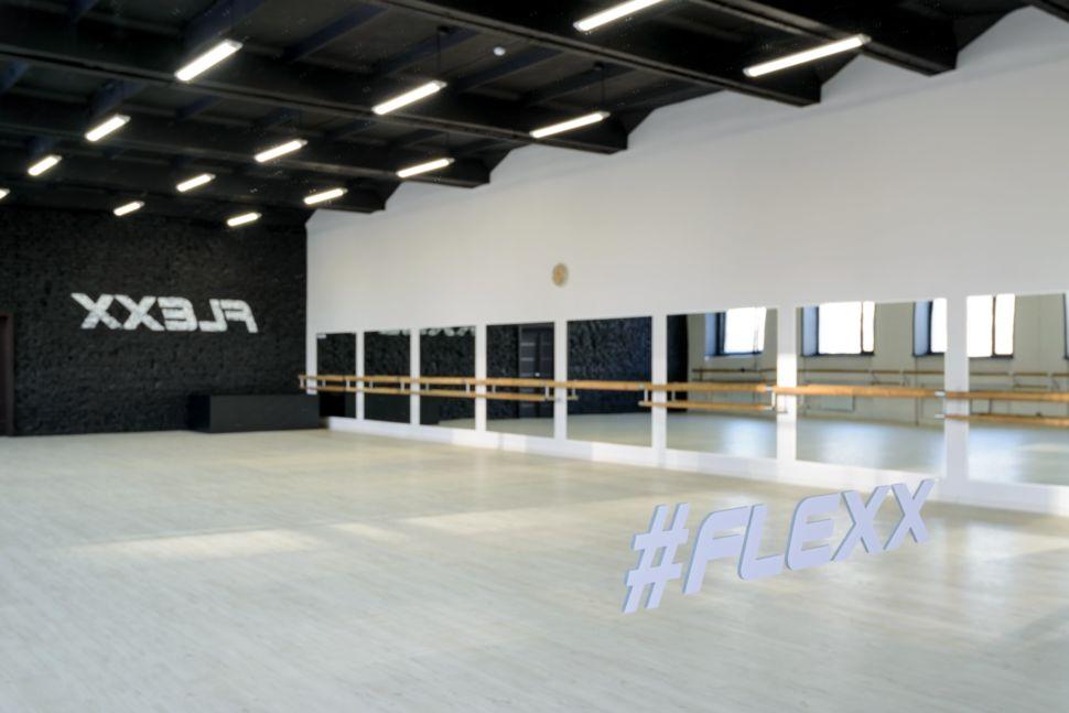 Фотография интерьера танцевального зала 210 кв.м, черный кирпич, белый логотип, зеркала, черный потолок, подвесные светильники, часы