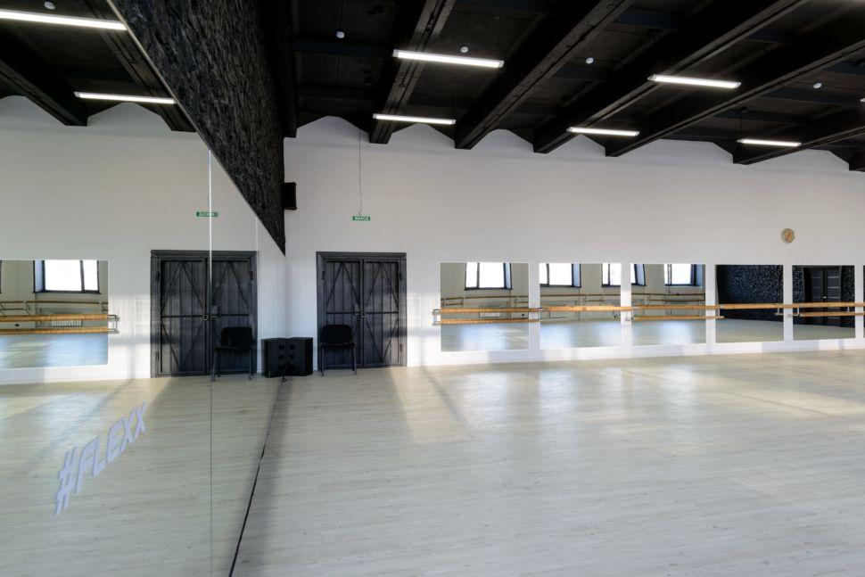 Фотография интерьера танцевального зала 210 кв.м, черный кирпич, белый логотип, зеркала, черный потолок, подвесные светильники, стул, паркет