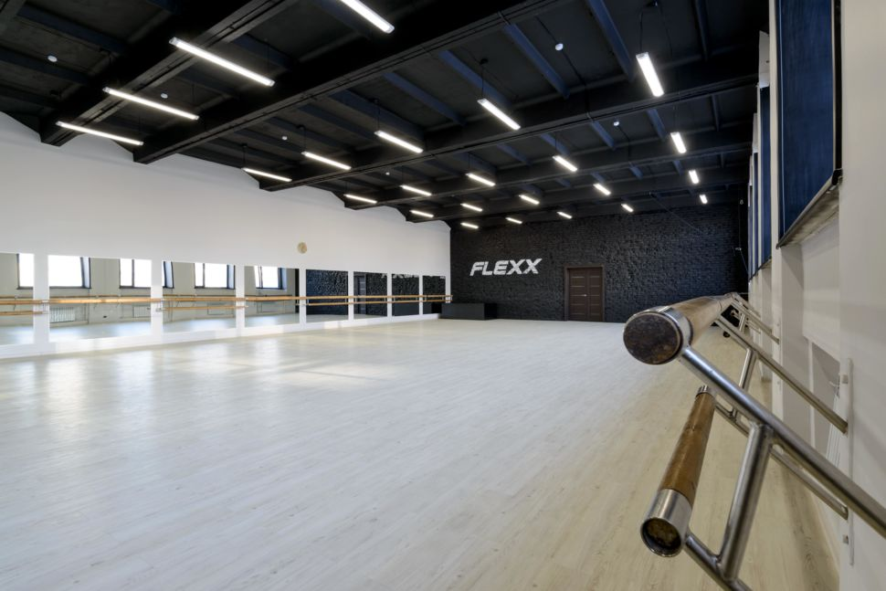 Фотография интерьера танцевального зала 210 кв.м, черный кирпич, белый логотип, зеркала, черный потолок, подвесные светильники, белые стены