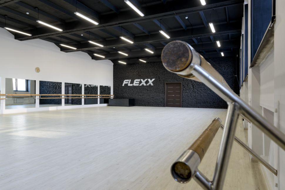 Фотография интерьера танцевального зала 210 кв.м, черный окрашенный кирпич, белый логотип, зеркала, черный потолок, подвесные светильники,