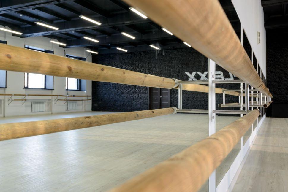Фотография интерьера танцевального зала 210 кв.м, черный кирпич, белый логотип, зеркала, черный потолок, подвесные светильники, брусья