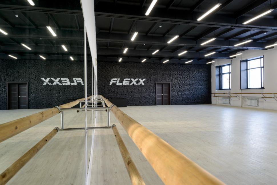 Фотография интерьера танцевального зала 210 кв.м, белый логотип, зеркала, черный окрашенный кирпич, подвесные светильники, отражение, черный потолок