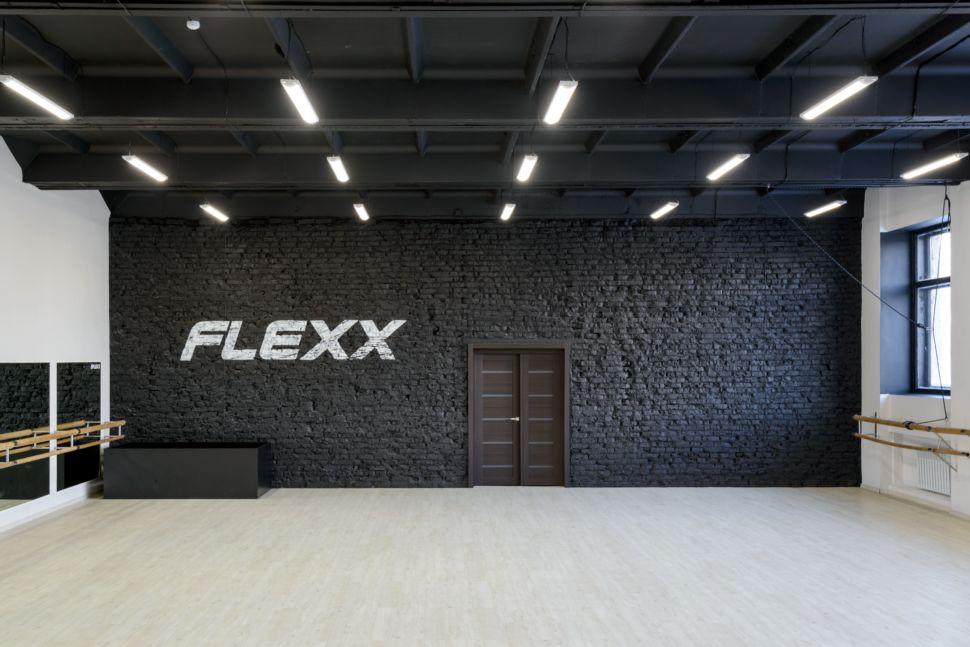 Фотография интерьера танцевального зала 210 кв.м, белый логотип, зеркала, черный окрашенный кирпич, подвесные светильники, тумба, черный потолок