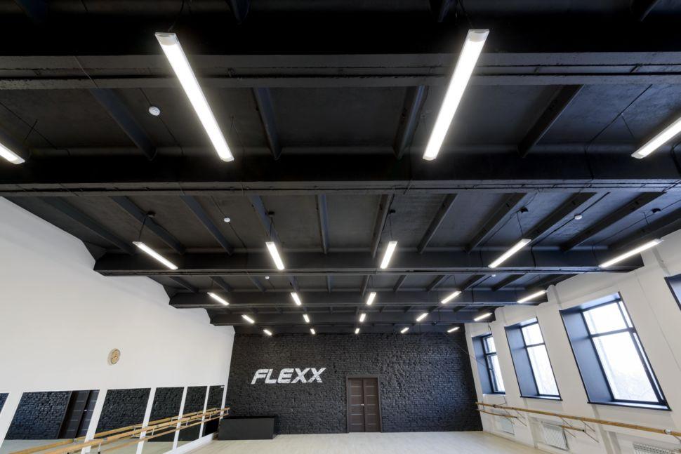 Фотография интерьера танцевального зала 210 кв.м, белый логотип, зеркала, черный окрашенный кирпич, подвесные светильники, балки, черный потолок