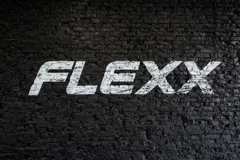 Фотография нарисованного логотипа, логотип нарисованный на черной кирпичной стене, белый логотип