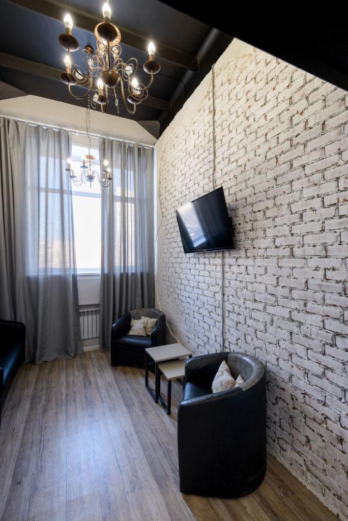 Фотография интерьера комнаты ожидания 13 кв.м в стиле лофт, кирпич, зона отдыха, кресло, журнальный столик, телевизор