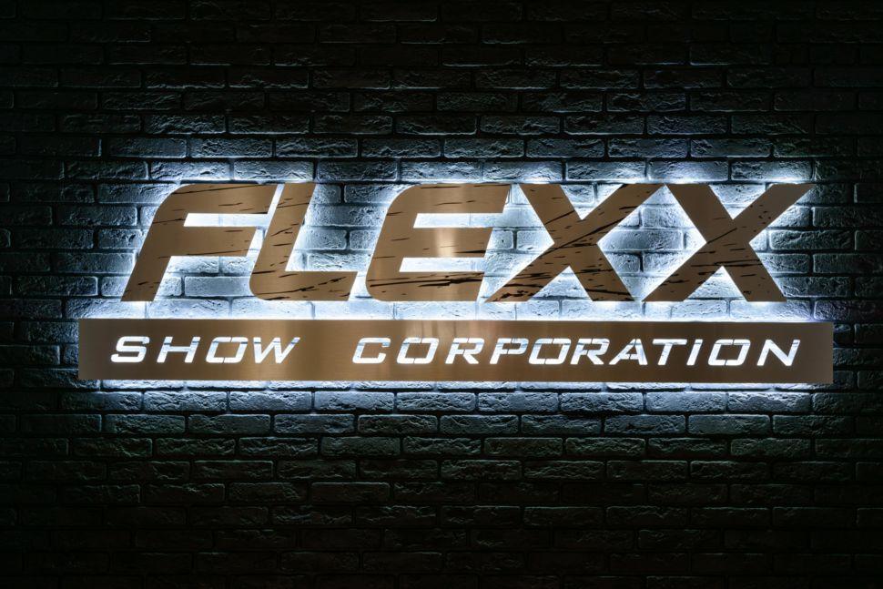 фото логотипа танцевальной студии в темных тонах, декоративная подсветка, черный кирпич, flexx
