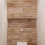 Интерьер санузла 2 кв.м в древесных и белых оттенках, унитаз, деревянные панели, плитка, потолочные светилники