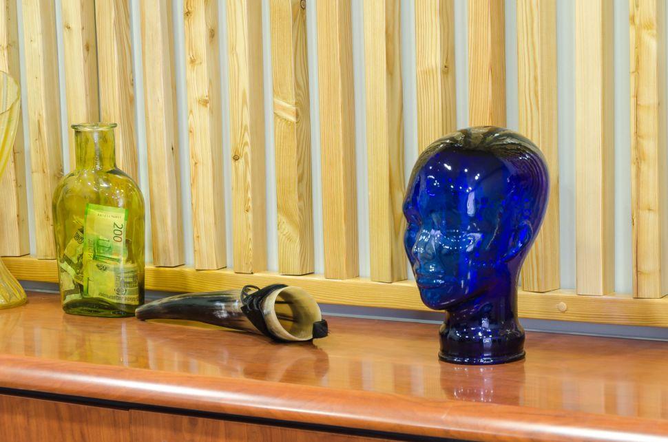 Фотография декора в офисе, декоративные деревянные рейки, комод под дерево, декор, рог, голова