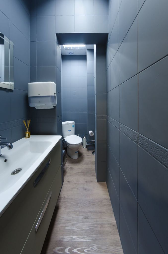 Фото санузла офисного помещения, керамическая плитка серого цвета, санузел, мойка, белый унитаз, раковина