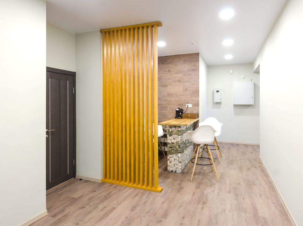 Фотография коридора 25 кв.м офисного помещения, барная стойка, белые барные стулья, пвх плитка, декоративная деревянная желтая перегородка, кофемашина