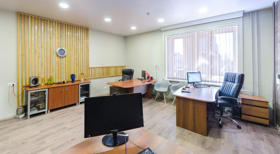 Фотография кабинета 32 кв.м, комод под дерево, декоративные деревянные рейки, часы, элементы декора, пвх плитка, компьютерные столы, черные офисные кресла